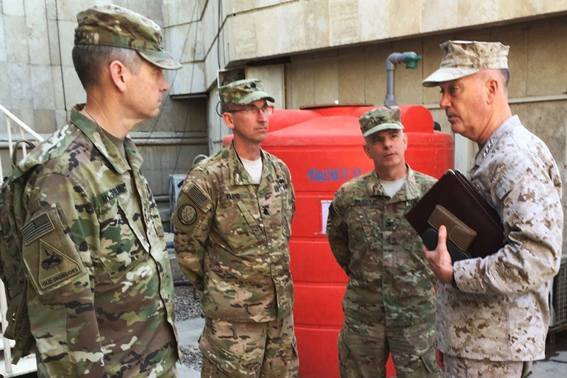 Marine Corps Gen. Joe Dunford, chairman of the Joint Chiefs of Staff, speaks with Army Col. Steve Warren, second from right