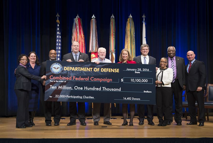 Deputy Defense Secretary Bob Work, fourth from left, presents a representation of a check of donated funds
