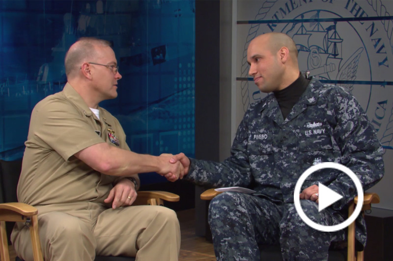 Screen grab of Petty Officer 2nd Class Dominique A. Pineiro and Cmdr. John Biery shaking hands.