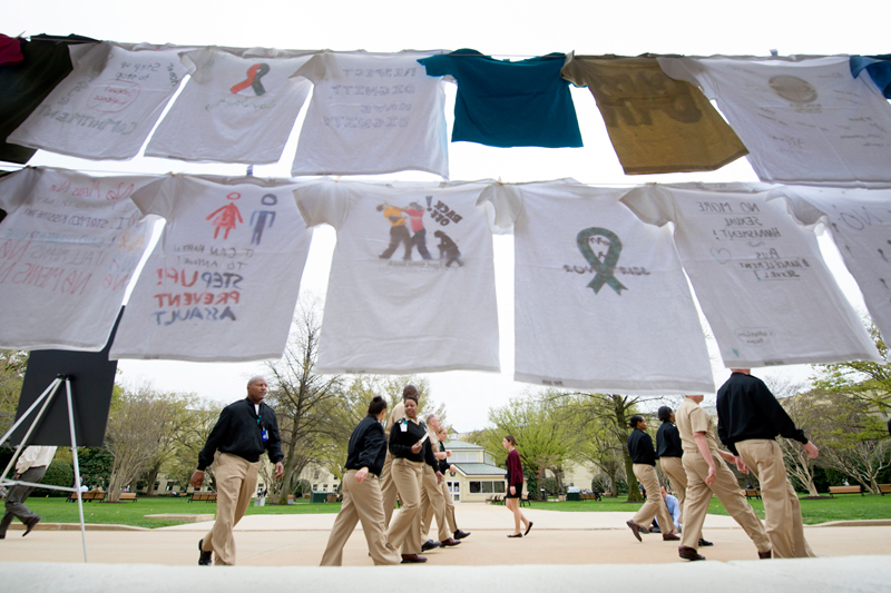Navy officers walk by a display of T-shirts decorated to support survivors of sexual assault