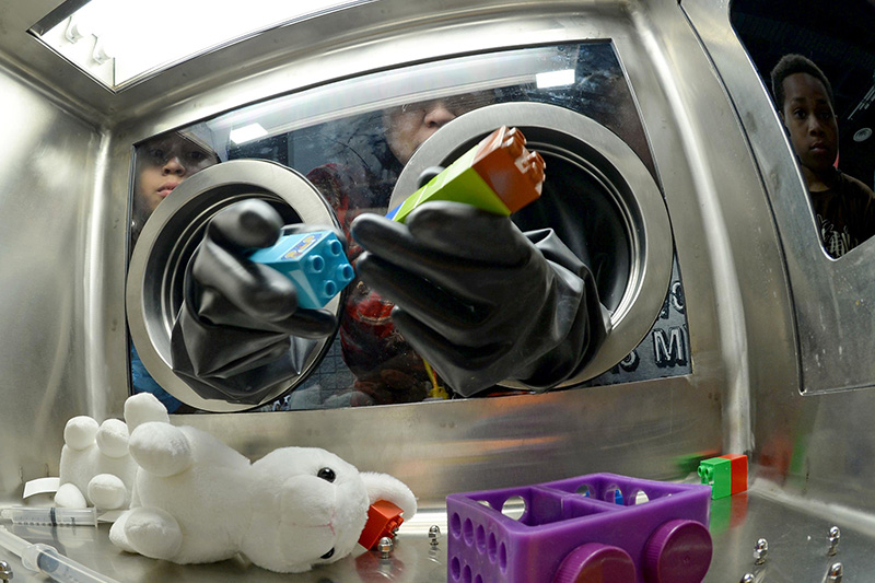 Students using a glove box to play an educational game.