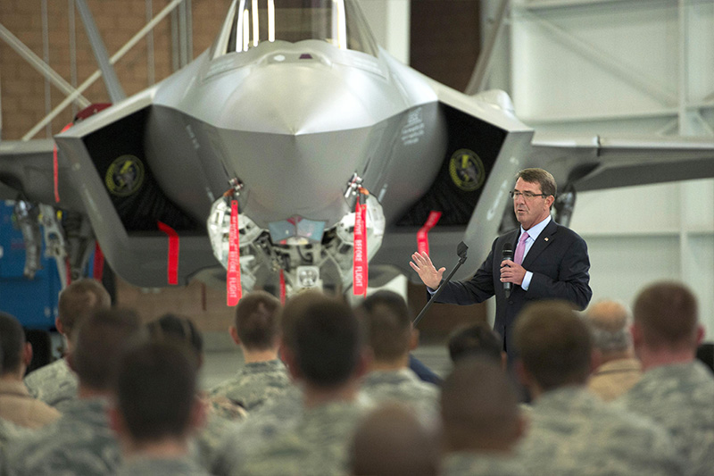 Defense Secretary Ash Carter speaking with service members with a jet in the background.