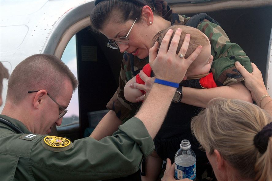 Navy Lt. Larry Anderson helps Air Force Col. Norma Allgood and her 15-month-old son out of an aircraft.