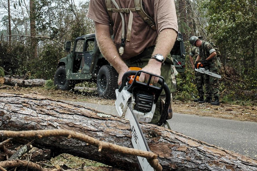 A Navy Seabee uses a chainsaw to remove fallen trees