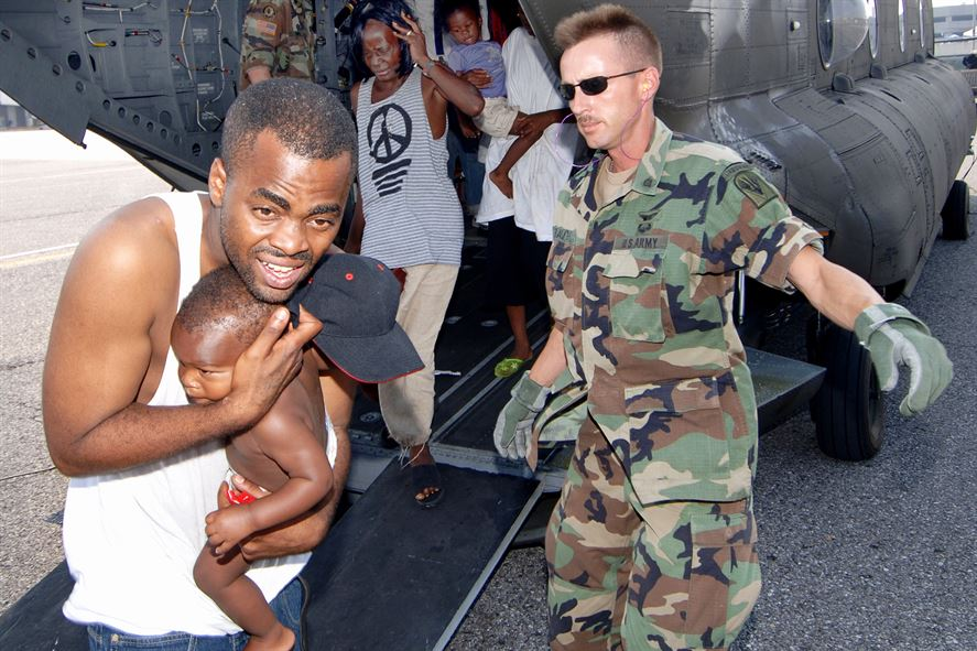 A soldier directs Hurricane Katrina victims as they exit the back of an Army CH-47 Chinook helicopter