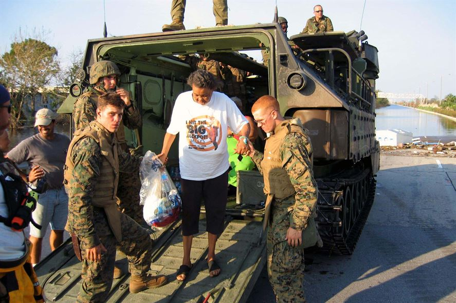 Marines assist Evelin Jenkins out of their assault amphibian vehicle