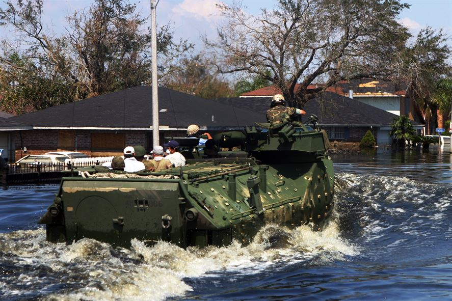 Marines in amphibious vehicles and infantrymen travel down the decimated streets of Orleans Parish conducting search-and-rescue operations