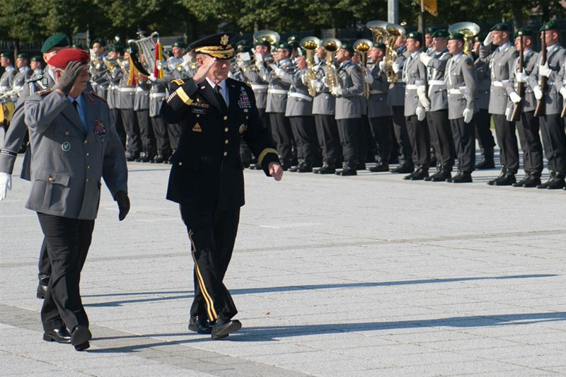 Army Gen. Martin E. Dempsey, chairman of the Joint Chiefs of Staff, and German Army Gen. Volker Wieker, chief of defense, salute during a pass-and-review ceremony of the German honor guard at the Ministry of Defense in Berlin.