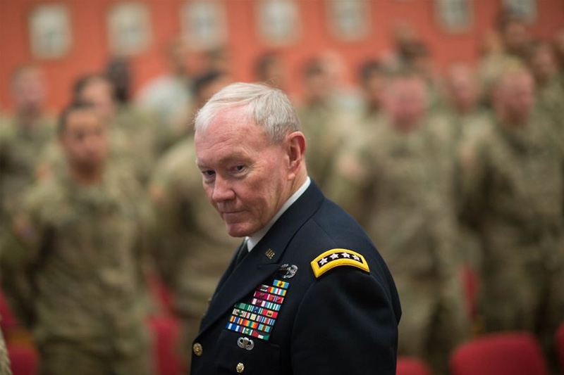 U.S. Army Gen. Martin E. Dempsey, chairman of the Joint Chiefs of Staff, gazing toward the camera with service men and women in the background.