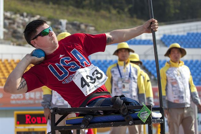 Disabled U.S. Athlete competing in CSIM Military World Games throws a shotput.