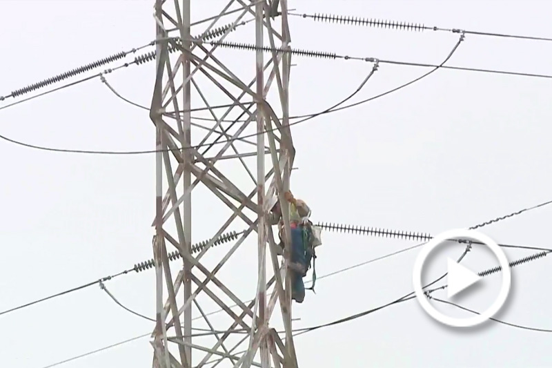 Screengrab of a technician working on fixing a powerline.