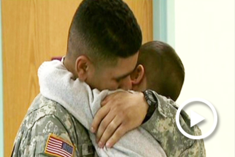 Screenshot of a soldier hugging a family member