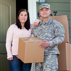 A military couple carries moving boxes outside their home.