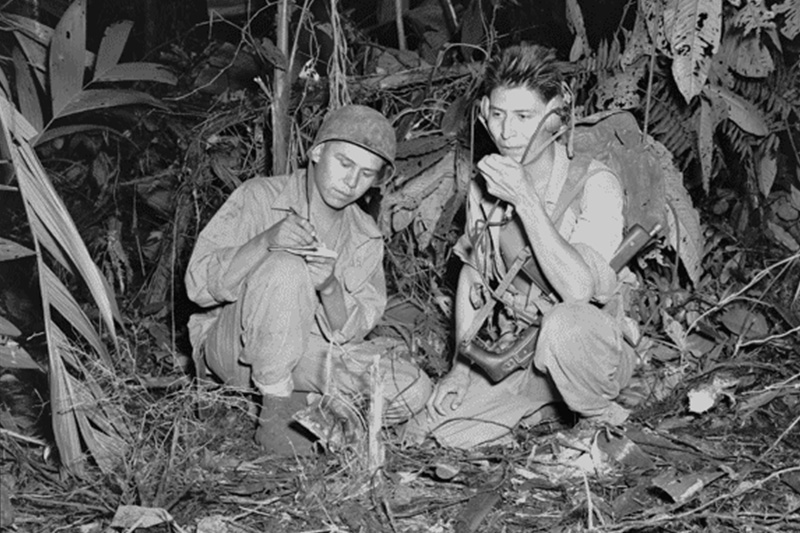 Navajo Code Talkers Marine Corps Cpl. Henry Bake, Jr. and Pfc. George H. Kirk use a portable radio near enemy lines.