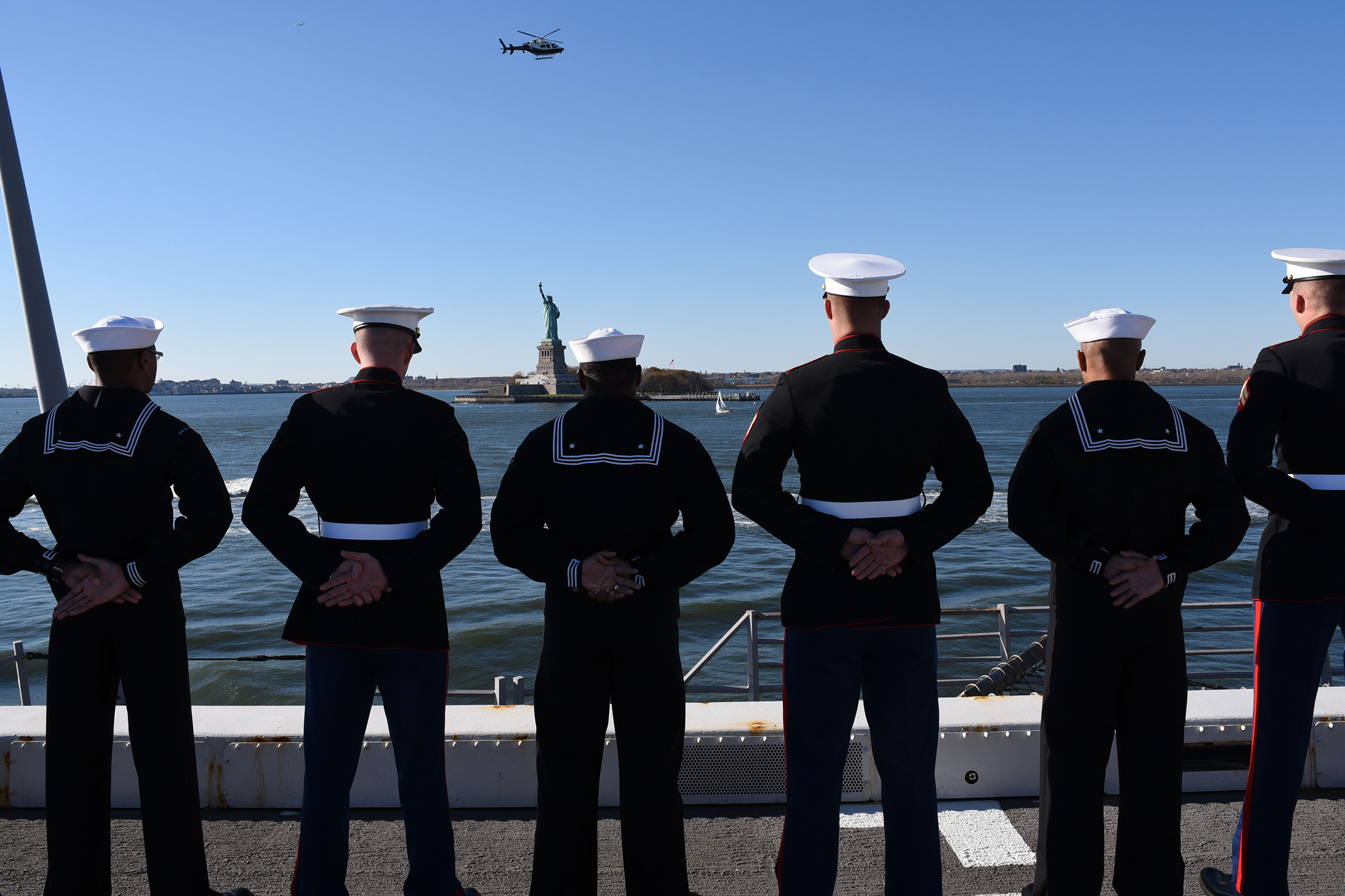 Sailors and Marines stand at parade rest while manning the rails.