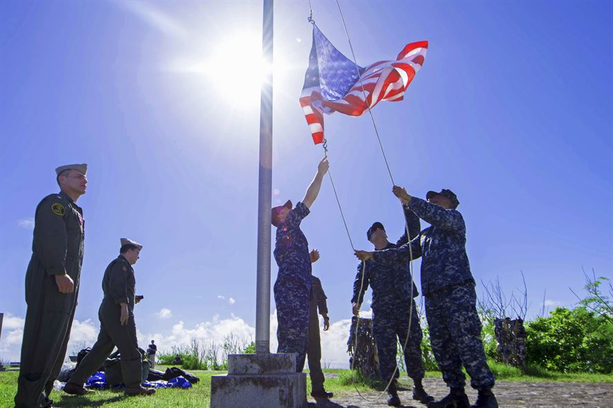 Three U.S. sailors in camouflage raise an American flag on a flagpole with the sun shining behind them.