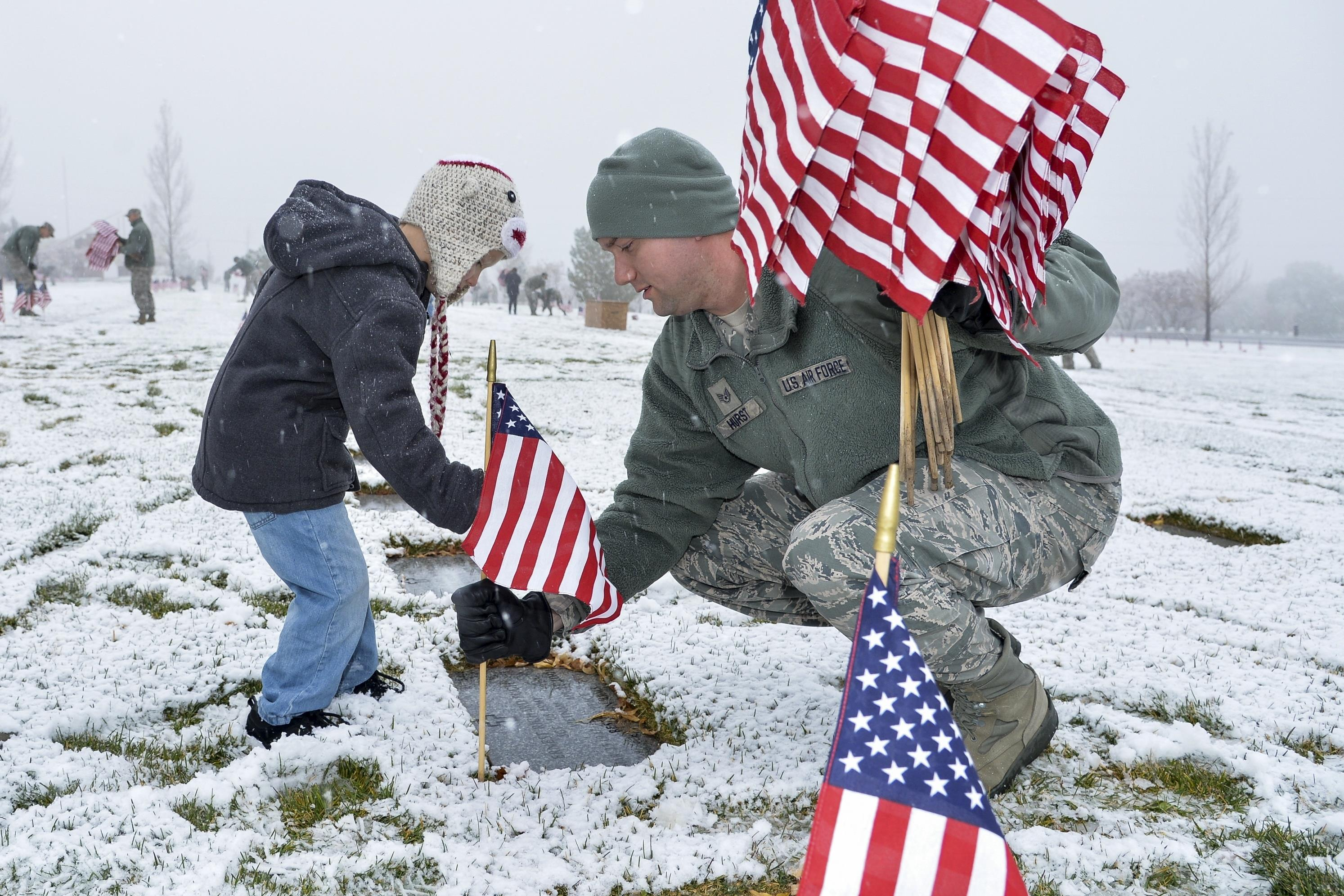 Air Force Staff Sgt. Louis Hurst and son, Ethan, place a flag beside a burial site