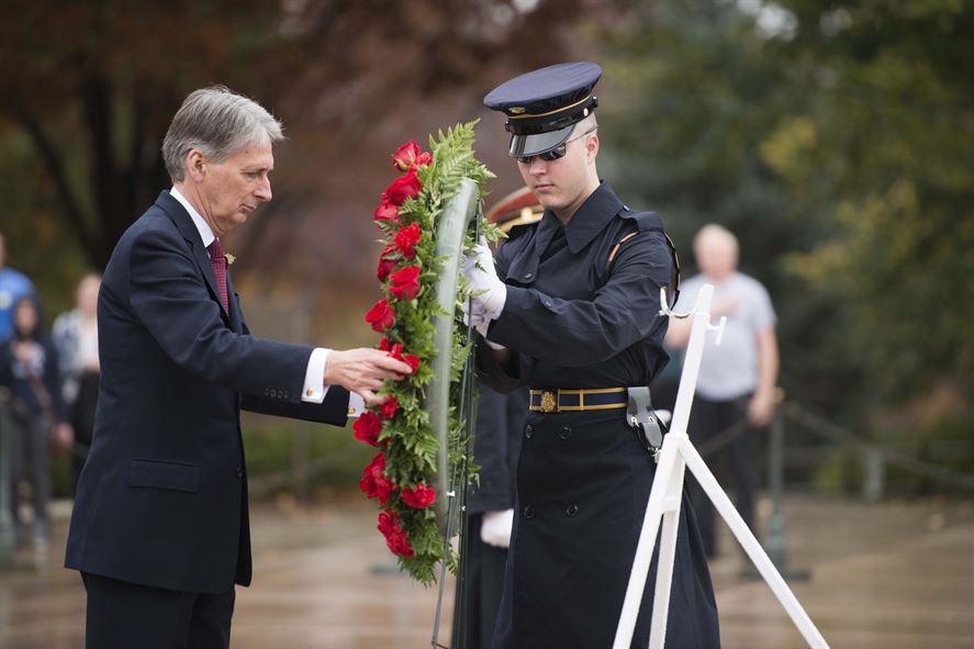 British Foreign Secretary Philip Hammond lays a large wreath with green leaves and red flowers with assistance from a young male marine.