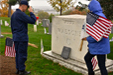 Uniformed military soluting a grave while another person holds an American flag.