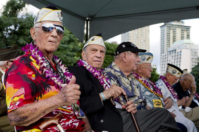 Bob Addott, left, giving a thumbs up as he and Thomas Petso attend the opening ceremony of the Pearl Harbor Memorial Parade on Fort DeRussy Park in Honolulu.