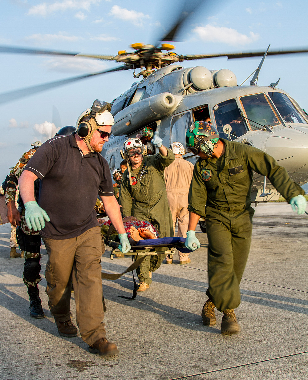 Relief personell carrying some affected by a disaster on a stretcher with a helicopter taking off behind them.