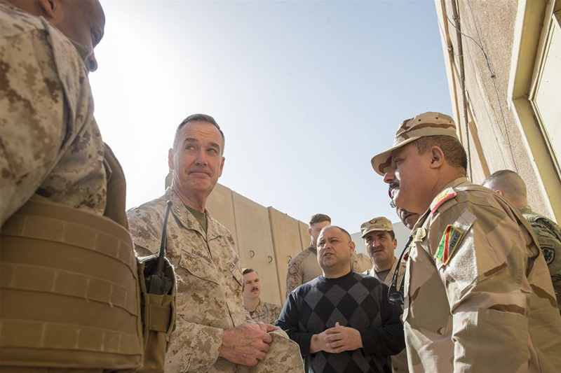 Photo of U.S. Marine Corps Gen. Joseph F. Dunford Jr., center left, chairman of the Joint Chiefs of Staff, listening to Marine Col. David Coconut, left, during a group discussion with Iraqi commanders.