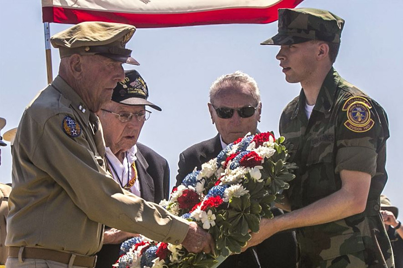 Photo of Former Army Air Corps Capt. Jerry Yellin, left, Navy Seabee Jack Lazere, center left, and Marine Carl DeHaven, veterans of the Battle of Iwo Jima, accepting a wreath from a member of the Young Marines group.