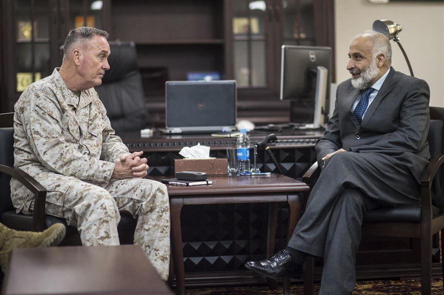 Marine Corps Gen. Joseph F. Dunford Jr., chairman of the Joint Chiefs of Staff, and Afghan Defense Minister Masoom Stanekzai sitting across from each other talking.