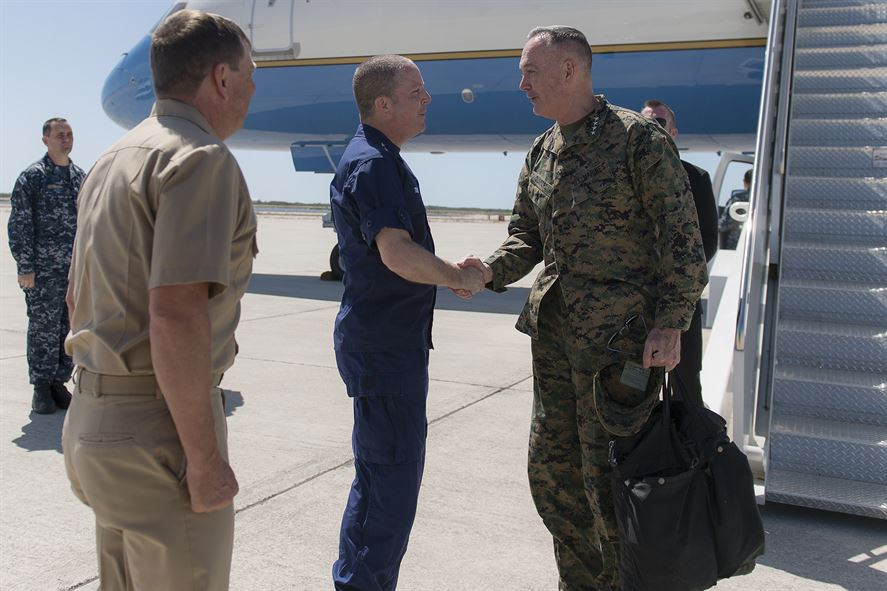 Marine Corps Gen. Joseph F. Dunford Jr., right, chairman of the Joint Chiefs of Staff, exchanges greetings with Coast Guard Rear Adm. Chris Tomney, director of Joint Interagency Task Force South