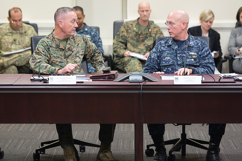 Marine Corps Gen. Joseph F. Dunford Jr., left, chairman of the Joint Chiefs of Staff, meets with Navy Adm. Kurt W. Tidd, commander, U.S. Southern Command, sitting behind a table looking at each other.