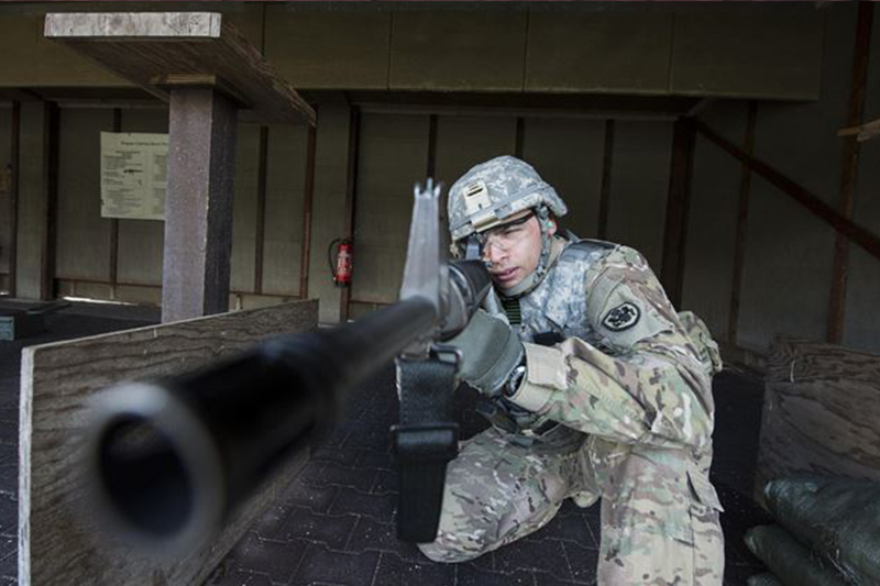 Army Spc. Demel Cooper sights an M16 rifle.
