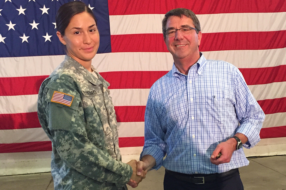 Defense Secretary Ash Carter shaking hands with Army Sgt. Terri Bluebird in front of an American flag