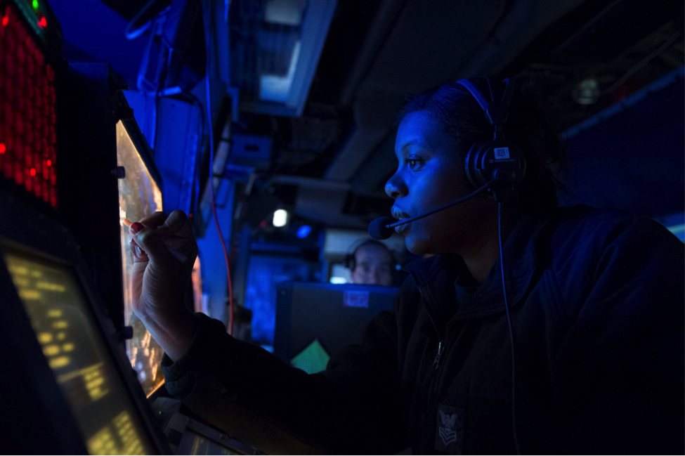 A closeup of a female African-American Navy officer wearing headphones with attached microphone in front of a panel, her face lit up blue by the glow.