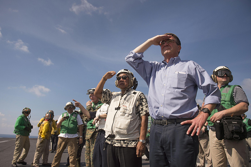 Defense Secretary Ash Carter and Philippine Defense Secretary Voltaire Gazmin standing on a flight deck shielding the sun from their eyes.
