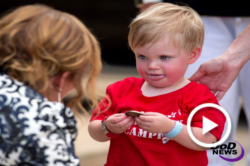 Screen grab of a child recieveing a coin.