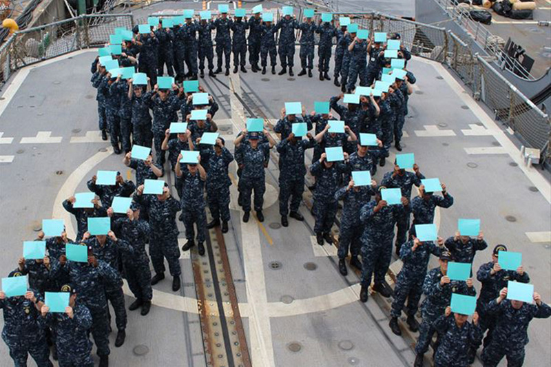 Sailors aboard the guided-missile cruiser USS Chancellorsville form a teal ribbon