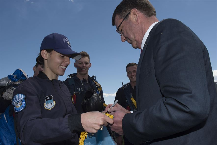Defense Secretary Ash Carter autographs a Secretary of Defense Flag