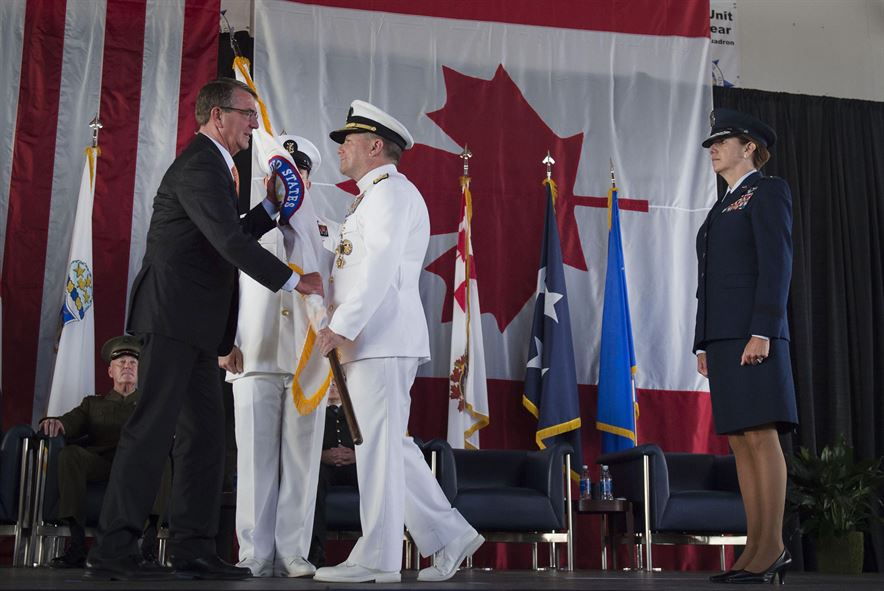 Navy Adm. Bill Gortney hands Defense Secretary Ash Carter a U.S. Northern Command flag