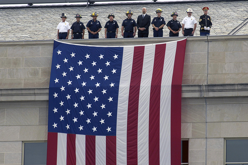 Representatives of police and firefighting units who were the first to respond to the 9/11 terrorist attack on the Pentagon, stand at the top of a large American flag suspended from the roof of the Pentagon.