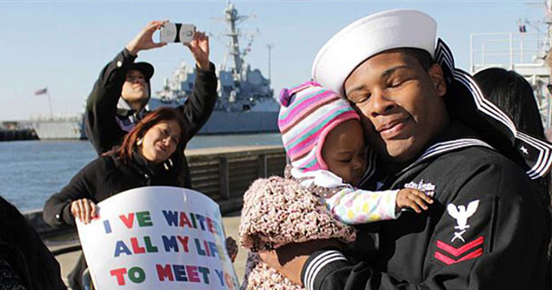 Navy Petty Officer 2nd Class Marcus Harris meets his daughter for the first time during a homecoming celebration for the guided-missile destroyer USS Barry in Norfolk, Va., Nov. 8, 2013.