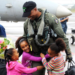 Navy Lt. Cmdr. Victor Glover greets his daughters at the Naval Air Facility Atsugi airfield, Japan, Oct. 26, 2010, during his squadron's homecoming celebration.