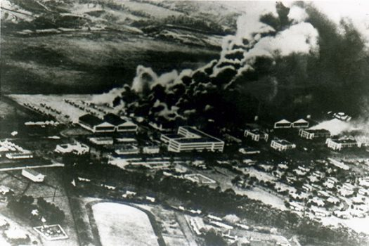 An aerial photo taken after the first wave of attacks shows a large cloud of smoke filling the sky over Wheeler Field.
