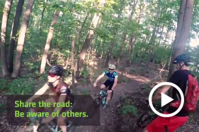 Screen grab of people riding bikes int he woods.