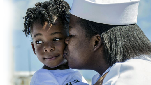 Navy Petty Officer 1st Class Ashley Johnson kisses her daughter
