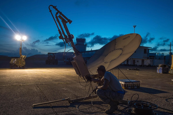 An airmen kneels next to a satellite communication antenna.