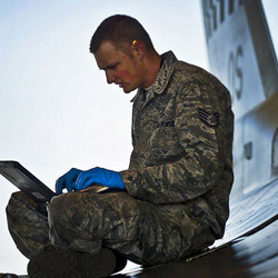 A service member sits cross-legged on the ground using a laptop.