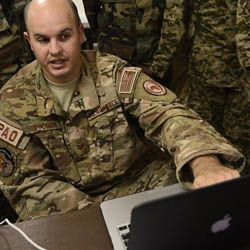 A service member gestures toward laptop.