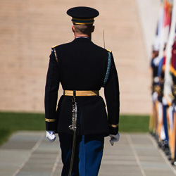 A service member stands at attention.