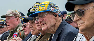 A line of elderly veterans wearing baseball caps decorated with pins.