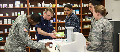 Five young enlisted members interacting around a table in a pharmacy.